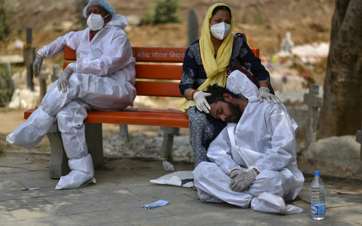 An exhausted health worker wearing personal protective equipment rests at a bench at a graveyard, in Delhi, India