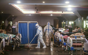 A health worker wearing a personal protective equipment suit cleans the floor inside a banquet hall temporarily converted into a Covid-19 coronavirus ward in New Delhi