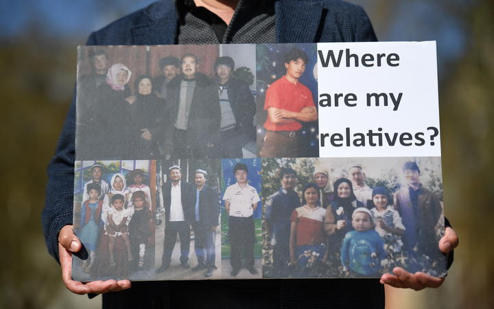 A member of the Uyghur community holds a placard as he joins a demonstration to call on the British parliament to vote to recognise alleged persecution of the Uyghur people as genocide and crimes against humanity in London on April 22, 2021.