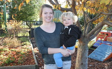 A photo of Brooke Gray and her son, Max, in the creche garden at Karanga Mai Young Parents College