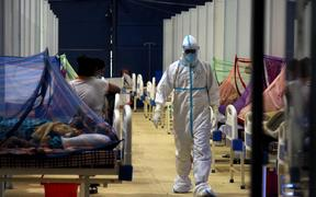 A doctor walks past Covid-19 patients at a makeshift facility created inside a sports complex, amidst the spread of coronavirus cases, in New Delhi, India on May 13, 2021.
