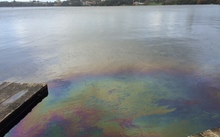 Rainbow coloured diesel stains the lake in the foreground while houses can be seen in the background