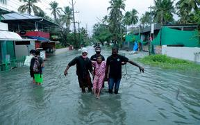 Police and rescue personnel evacuate a local resident through a flooded street in a coastal area after heavy rains under the influence of cyclone 'Tauktae' in Kochi on May 14, 2021.