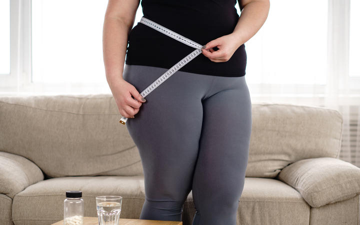 obese woman with pills and measure tape