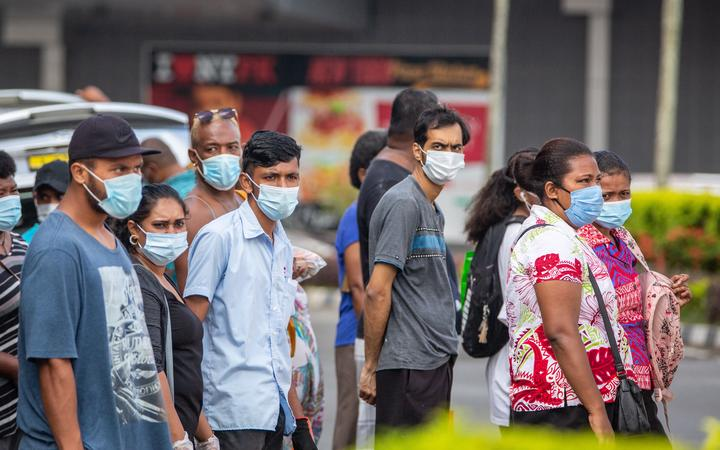This picture taken on April 24, 2021 shows residents wearing face masks waiting to cross the main road in the Fijian capital Suva ahead of an expected lockdown in the capital due to a Covid-19 spike. (Photo by Leon LORD / AFP)