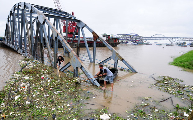 Chinese workers clear away garbage floating on the flooded Yangtze River.