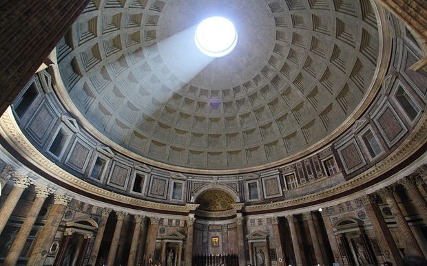 The inside of the Pantheon with light shining down from the Oculus on to tourists standing beneath