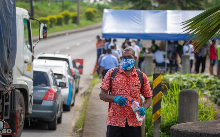 """This picture taken on April 26, 2021 shows security officers checking cars along a road in Suva after the Fijian capital entered a 14-day lockdown following a Covid-19 spike following a """"superspreader"""" funeral event."""