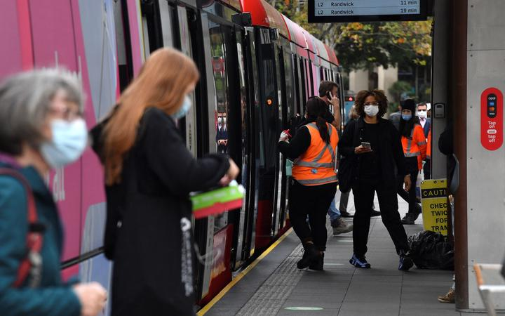 Passengers wearing face masks alight from a metro in Sydney on June 23, 2021, as residents were largely banned from leaving the city to stop a growing outbreak of the highly contagious Delta Covid-19 variant spreading to other regions.