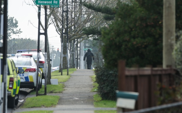 A man wearing protective gear heads towards the property at the centre of the cordon.