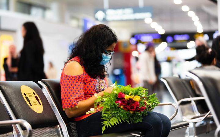 A woman waiting at Auckland Airport for passengers to disembark from the first flight from Sydney to Auckland under the trans-Tasman bubble arrangement.