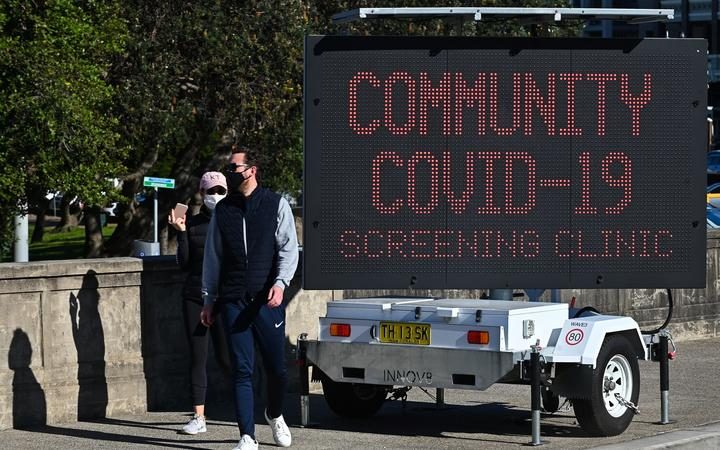 People walk past a sign for a Covid-19 testing clinic at Bondi Beach in Sydney 27 June, 2021.