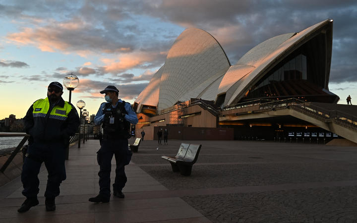 Police officers walk past The Sydney Opera House during the first day of lockdown in Sydney, Australia.