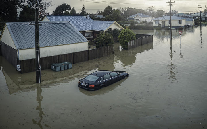 A partly-submerged car outside flooded houses on Disraeli St, Westport.