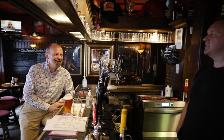 A customer drinks a pint standing at the bar of a pub in central London on July 19, 2021 as coronavirus restrictions are lifted.
