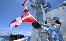 A Chinese navy soldier hangs signal flags on missile destroyer Hefei during a military exercise in the South China Sea.