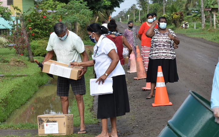 People lining up to get food supplied from Save the Children on the main island Viti Levu.