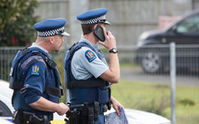 Two police stand in the middle of the street inside a cordon in South Auckland.