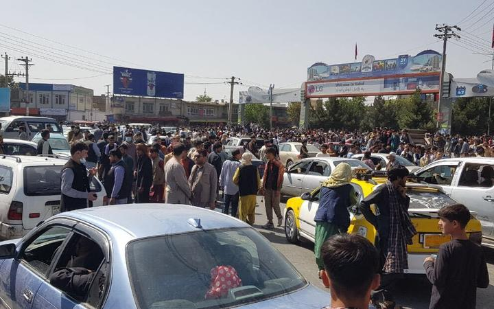 Afghans crowd at the tarmac of the Kabul airport.