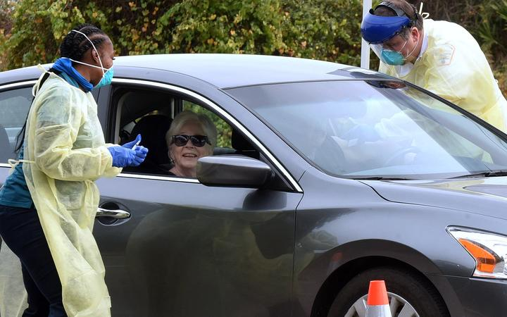 Health workers administer the Moderna COVID-19 vaccine to a couple in a car at a drive-thru vaccination event for residents 65 and older at Dewey O. Boster Park and Sports Complex on January 7, 2021 in Deltona, Florida.