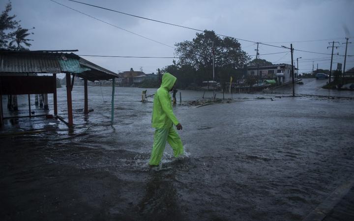 El 21 de agosto de 2021, un hombre camina por una calle inundada en Veracruz, México, debido a las fuertes lluvias provocadas por el huracán Grace en Decolatla.