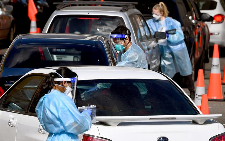 Medical personnel take details at a drive-through Covid-19 testing station in Melbourne on August 19, 2021, as Australia battles an outbreak of the Delta variant of coronavirus.