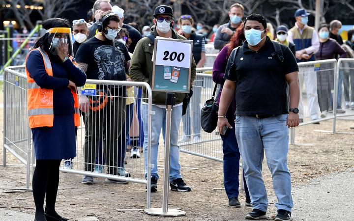 People wait in a queue for their Covid-19 coronavirus vaccination in Sydney on August 18, 2021. (Photo by Saeed KHAN / AFP)