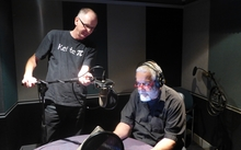 William gets ready to record while his producer makes a fine adjustment to his microphone placement.