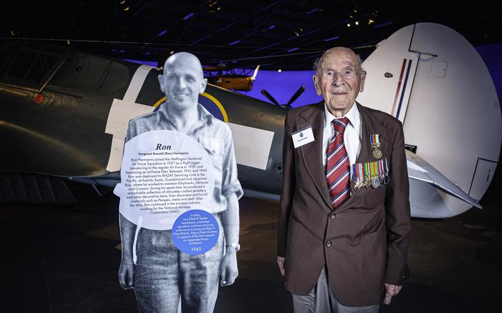Ron Harmans stands with his little figure at the New Zealand Air Force Museum in 2019.