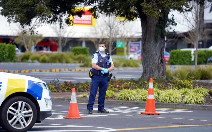 Police keep watch outside the Countdown supermarket at Lynn Mall in Auckland on September 4, 2021, the day after an IS-inspired attacker injured six people in a knife rampage before being shot dead by undercover police.