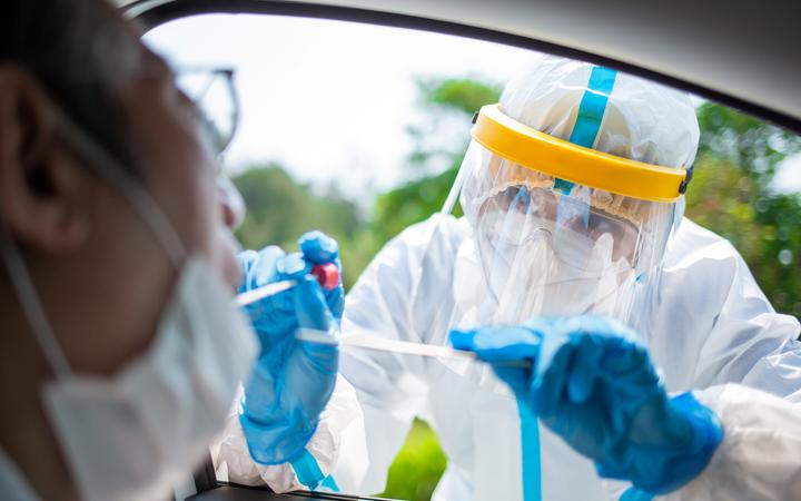 Corona virus test - A medical worker sweeps the throat for a corona virus sample from a potentially infected elderly person in a gown or protective suit and surgical face mask.