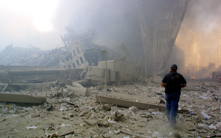 A man walks through the rubble after the collapse of New York's first World Trade Center tower on September 11, 2001.