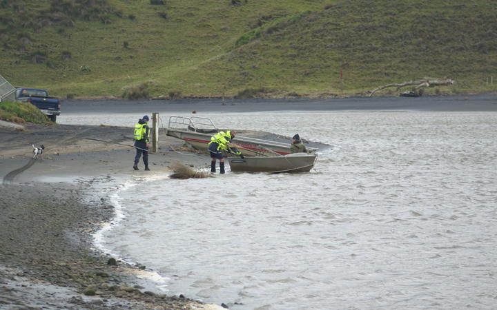 Locals and Landsar personnel at Kiritehere Beach where Thomas Phillips' car was found.