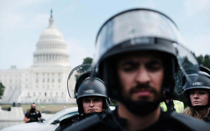 High security, small turnout at US rally supporting 6 Jan rioters