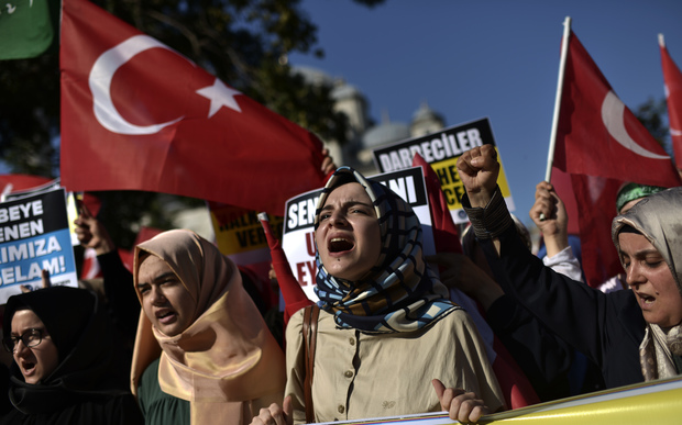 Pro-Erdogan protesters wave Turkish flags and shout slogans as they demonstrate in Istanbul in support the government on July 16, 2016, following a failed coup attempt.