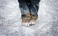A child's bare feet on a gravel road