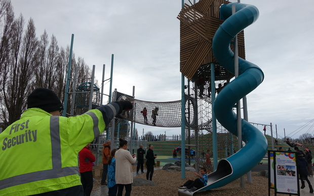 A security guard watches over children at Margaret Mahy Playground.