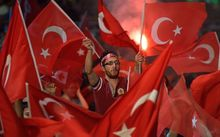 A man waves a Turkish flags during a meeting in support of the Turkish president on Taksim Square on 19 July.