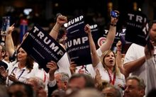 Delegates hold signs in support of Donald Trump during roll call at the Republican National Convention.