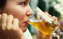 A woman drinks a glass of beer at a restaurant (file)