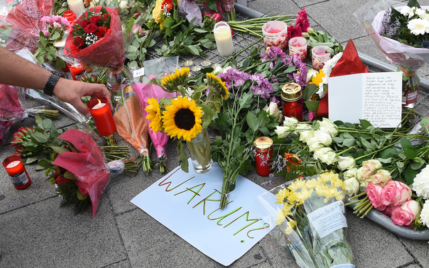 "A candle is placed next to a sign reading ""Why"" and flowers laid down for the victims of the shooting."