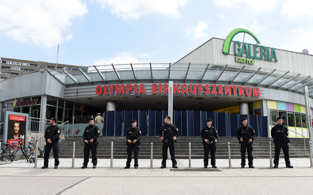 Policemen stand in front of the Olympia-Einkaufszentrum shopping centre in Munich one day after the attack.