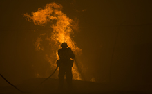 A firefighter hoses down burning pipes near a water tank at the Sand Fire near Santa Clarita, California.