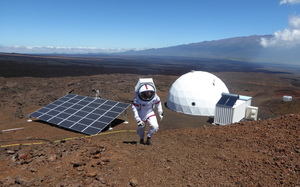 Sheyna Gifford walking outside her simulated Mars base in a spacesuit. The base is an white dome and there are solar panels in front of it.