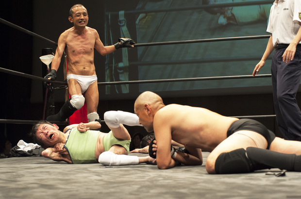 "Shintaro Yano ( ""Sambo"" Shintaro) watches on as tag-team partner L'Amant delivers a kick to able-bodied ""Antithesis"" Kitajima's face."