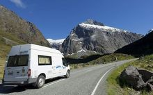 Campervan on the road, snow-capped mountains can be seen in the background