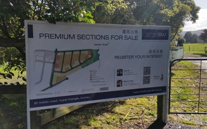 A sign posted at the Huapai Triangle, offering 'premium sections'.