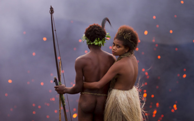 A man and a woman in traditional Ni-Vanuatu dress stand near the mouth of of an erupting volcano