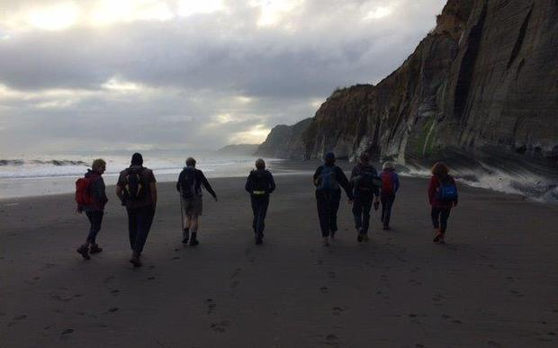 Trampers on a beach section of the Whitecliffs walkway