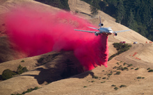 A plane drops fire retardant while battling the Soberanes Fire in Carmel Highlands, California on 23 July 2016.